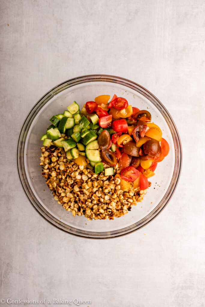 all of the ingredients for corn tomato cucumber salad in a large glass bowl
