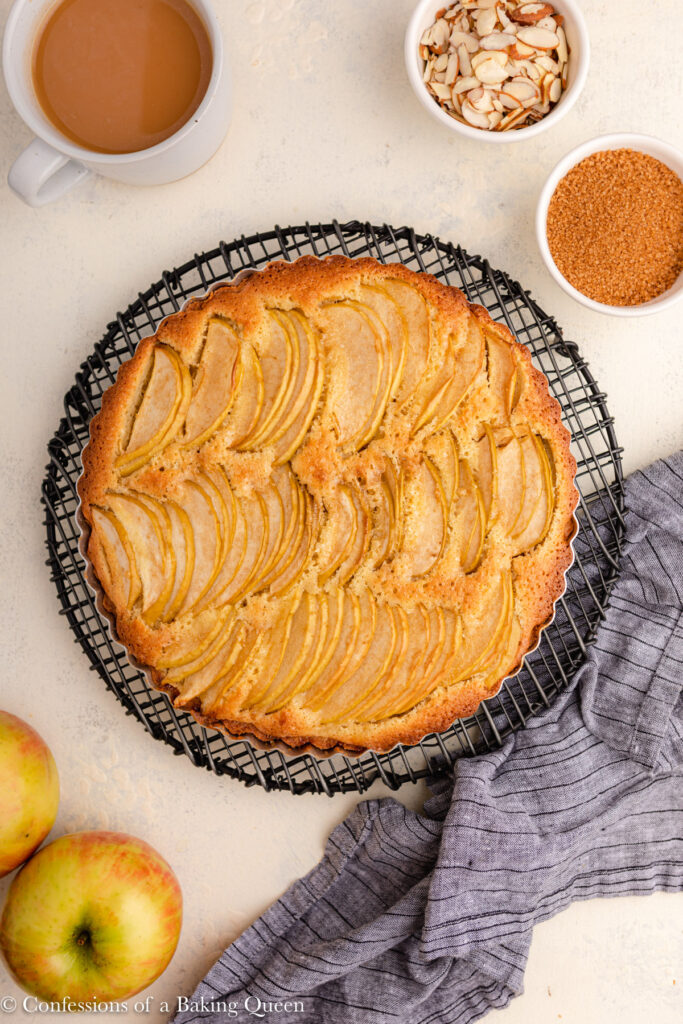 apple frangipane tart cooling on a wire rack next to a cup of coffee, apples, bowl of sugar, and bowl of almonds