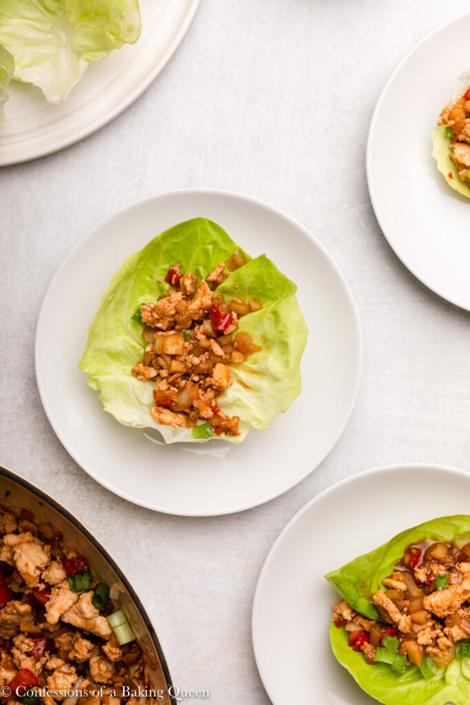 chicken lettuce cup on a white plate next to more plates of lettuce cups and skillet full of chicken mixture on a grey surface