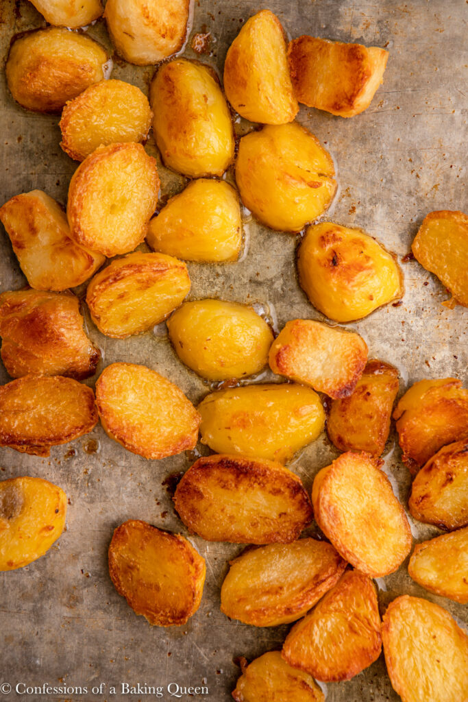 close up of roast potatoes just baked on a metal sheet pan on a grey surface