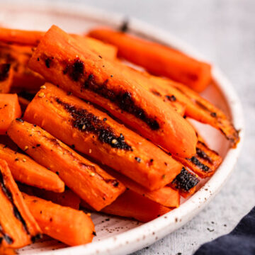 close up of roasted carrots on white and brown speckled plate on a grey surface with a navy blue linen