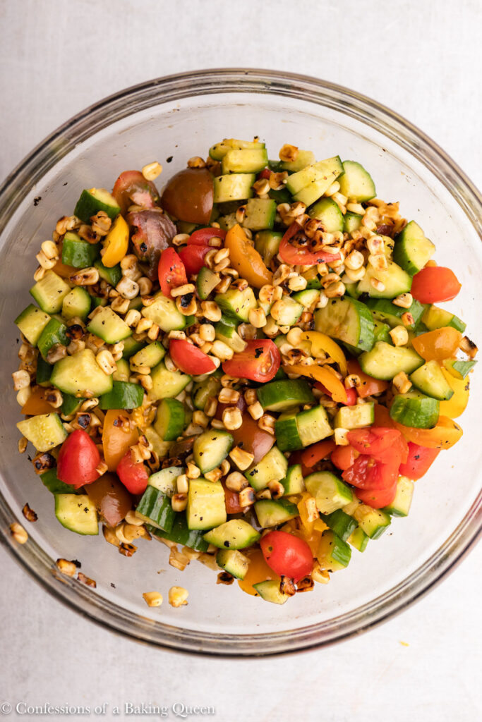 close up of tomato cucumber corn salad in a glass bowl