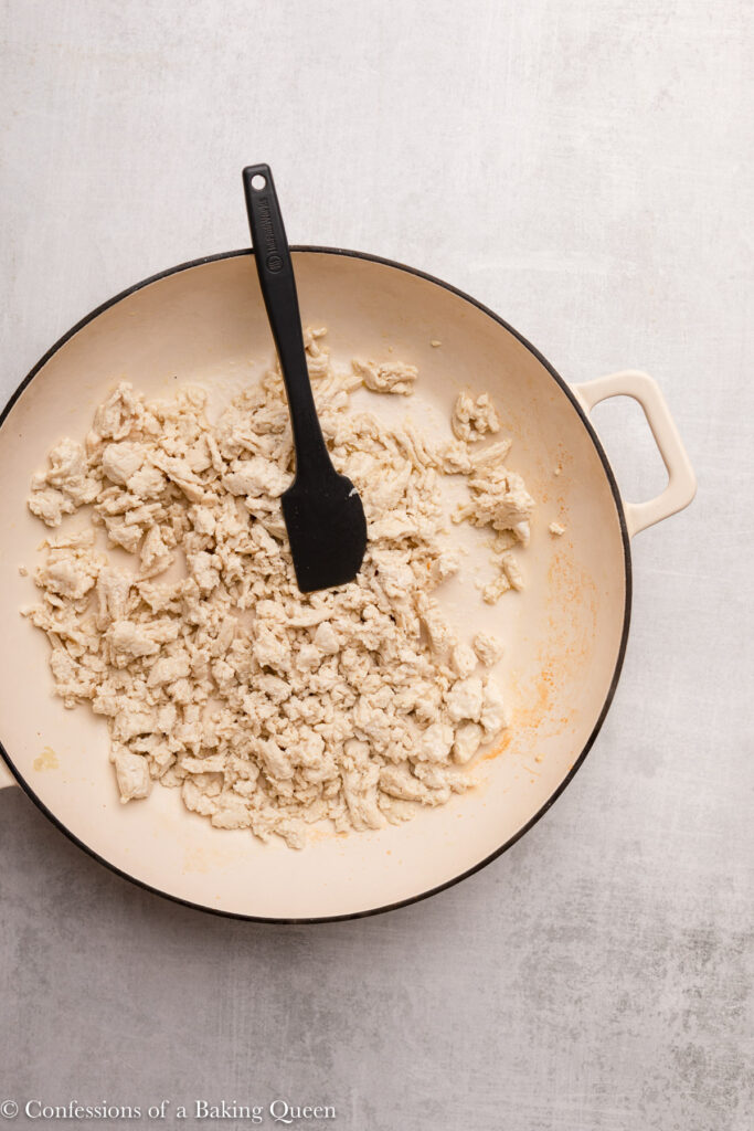 cream enameled cast iron skillet with bronwed ground chicken on a grey surface