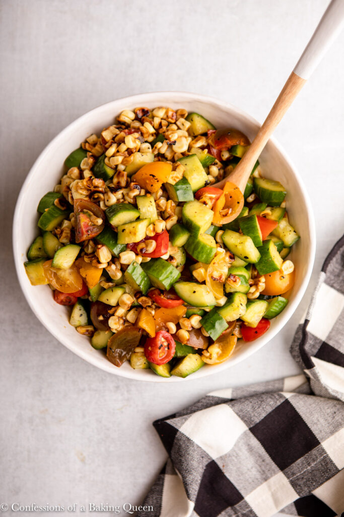 cucumber, corn, and tomato salad in a white bowl with a wooden spoon next to a black and white checkered towel