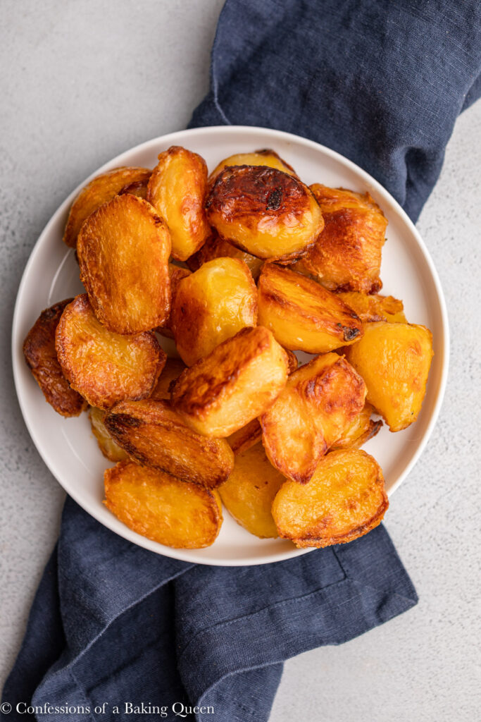 english roast potatoes on a white plate on top of a navy blue linen on a grey surface