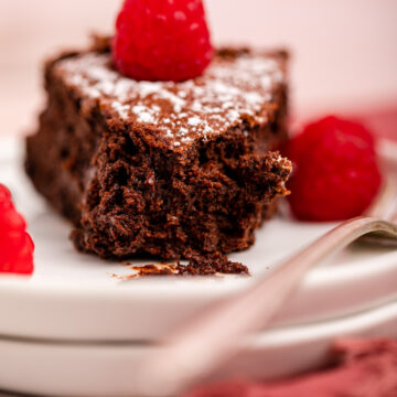 flourless chocolate cake on a white plate with raspberries and a fork