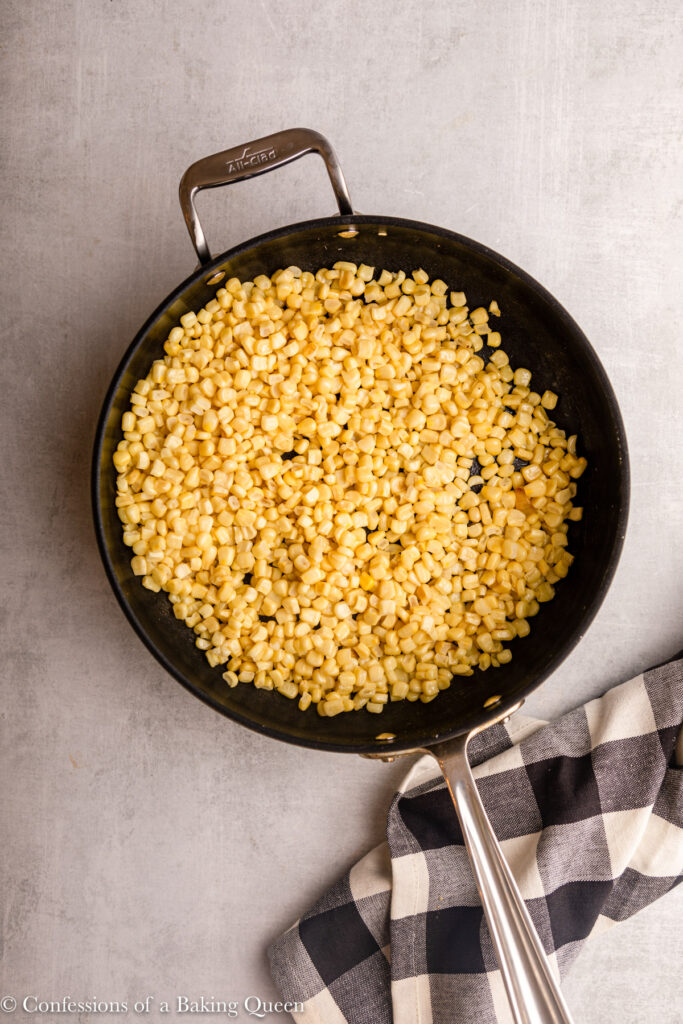 frozen corn in a large skillet next to a black and white checkered towel