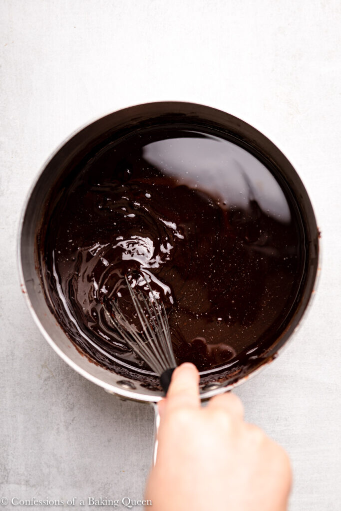 hand whisking vegetable oil into chocolate mixture in a large pot