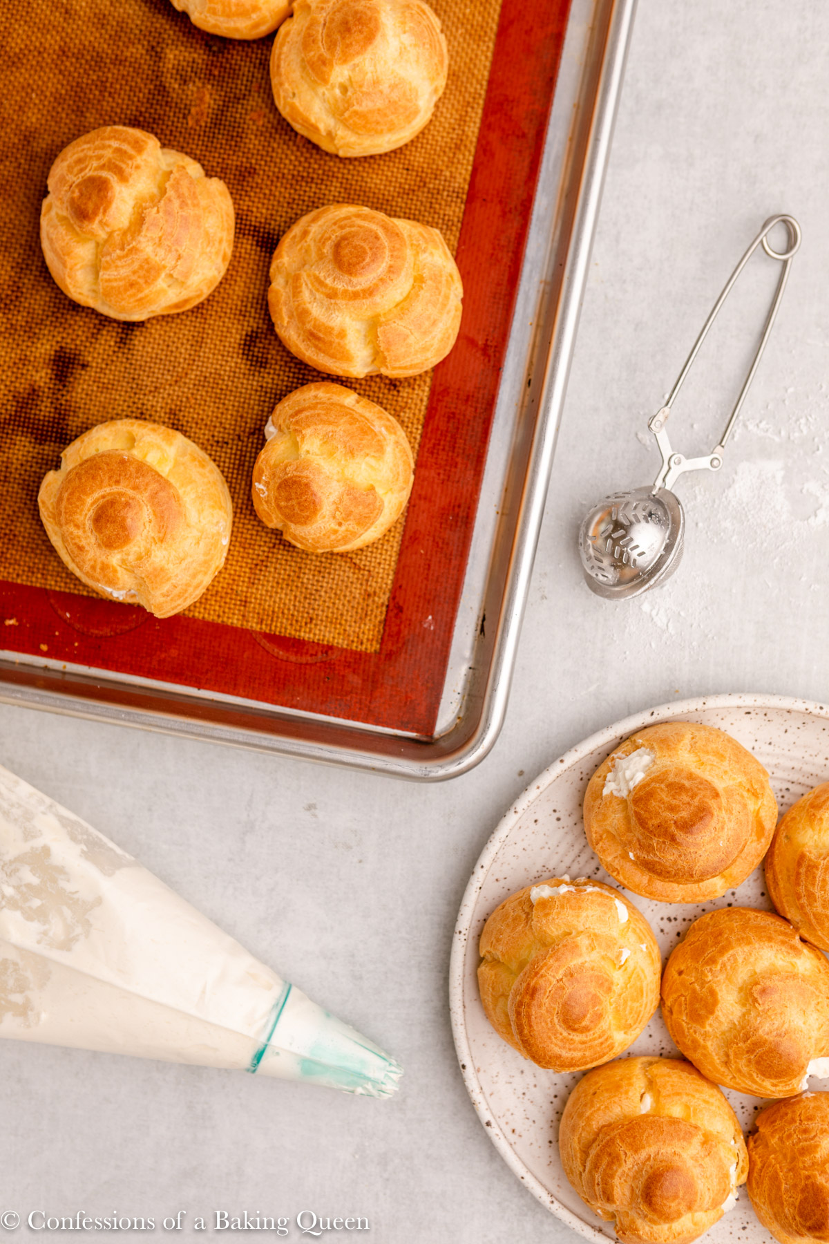 piping bag with whipped cream and a blue piping tip next to a plate full of cream puffs, a baking tray of choux pastry, and a powdered sugar sifter