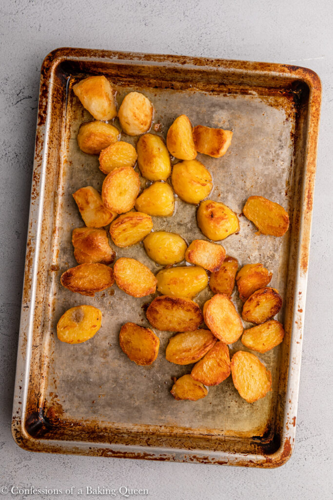 roast potatoes just baked on a metal sheet pan on a grey surface