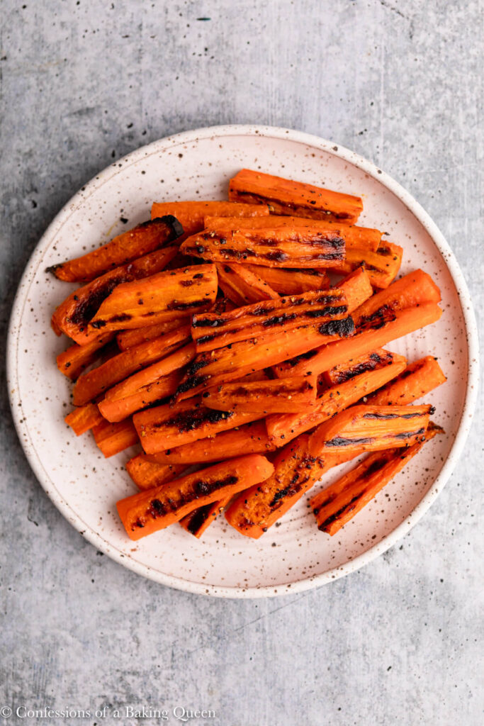 roasted carrots on white and brown speckled plate on a grey surface