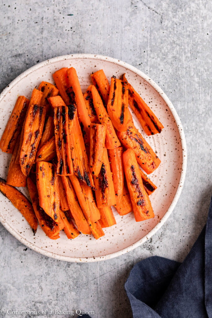 roasted carrots on white and brown speckled plate on a grey surface with a navy blue linen
