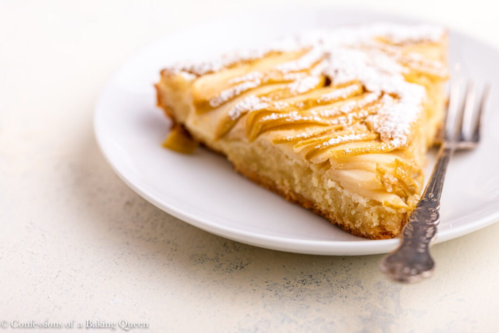 slice of apple almond tart with a fork on a white plate (