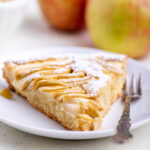 slice of apple almond tart with a fork on a white plate with apples in the background