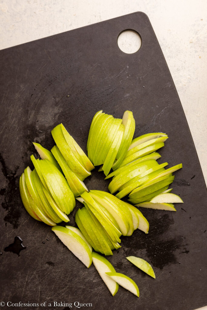 sliced green apples on a black cutting board