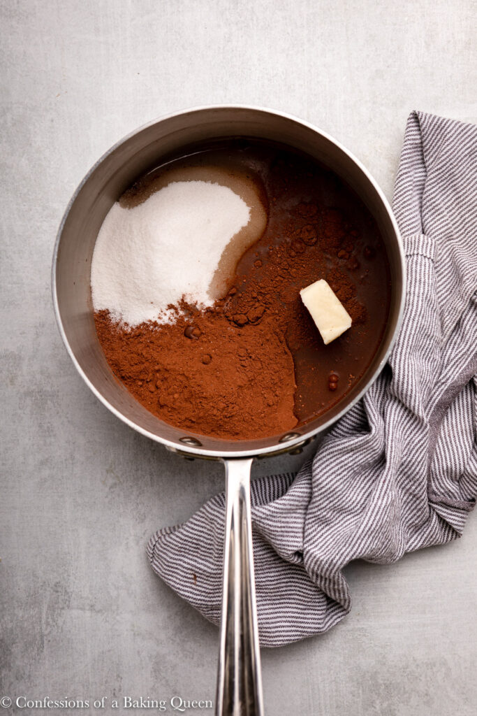 sugar, cocoa powder, water, and butter in a metal pot on a grey surface