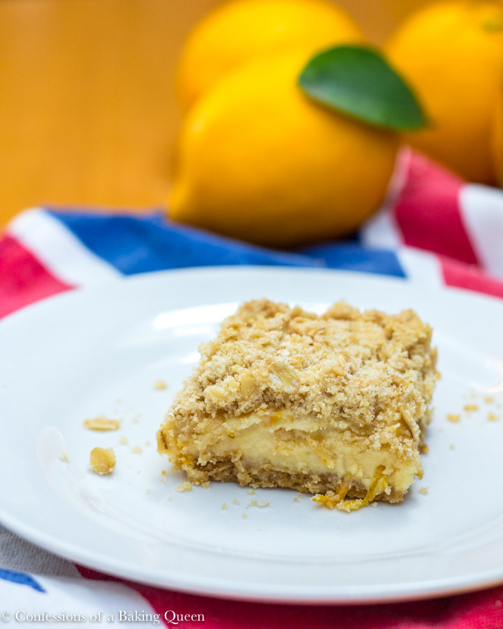 lemon crumb bar on white plate on a union jack tea towel on a wood table with three lemons