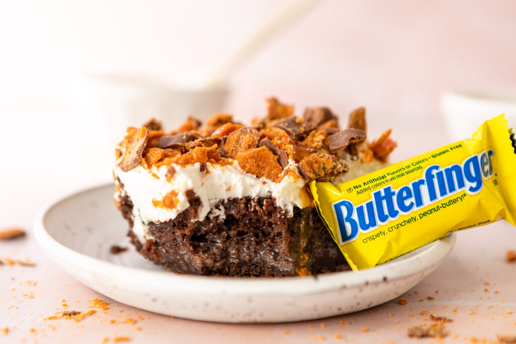 butterfinger poke cakes slice on a small white plate with a butterfinger fun size bar on a pink surface