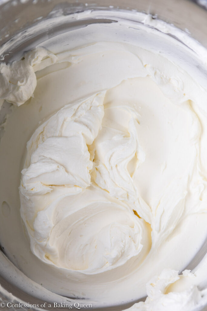 close up of cream cheese whipped cream frosting - in a metal bowl with a wire whisk on a grey surface