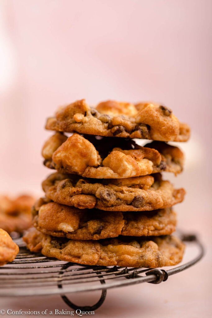 cornflake marshmallow cookies stacked on top of each other on a wire rack on a pink background