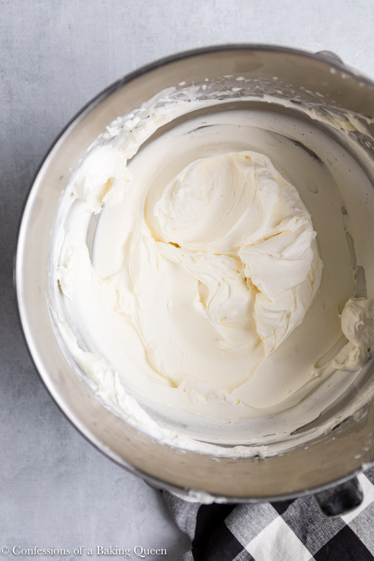 cream cheese whipped cream frosting- in a metal bowl with a wire whisk on a grey surface with a white and black linen