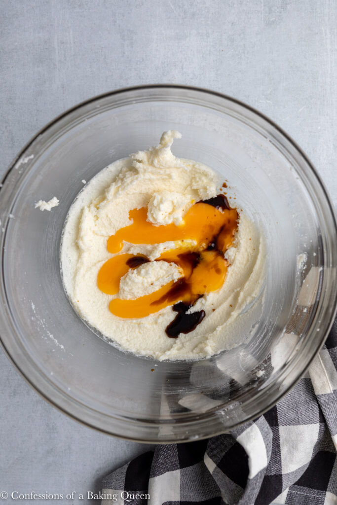 creamed sugar and butter with an egg and vanilla added in a glass bowl on a grey surface next to a black and white linen