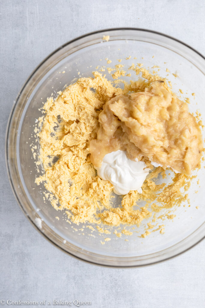 mashed banana and sour cream added to wet ingredients in a glass bowl on a grey surface