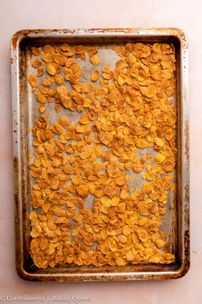 metal sheet pan with cornflakes toasted on a pink surface