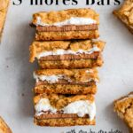 smores bar pieces stacked on top of each other on a grey surface next to more s'mores bars