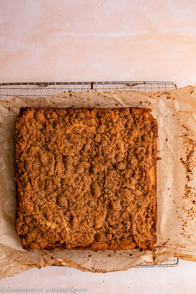 sour cream coffee cake cooling on a piece of parchment paper on a wire rack on a pink surface