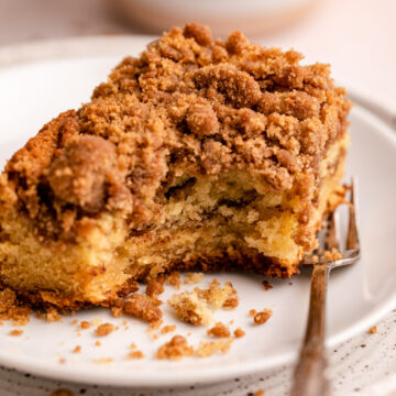 sour cream coffee cake slice half eaten on a plate with a fork on top of another plate with a cup of coffee in the background on a white surface