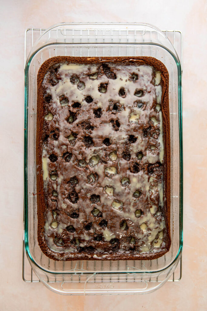 sweetened condensed milk and caramel mixture soaking into a chocolate sheet cake in a glass pan on a wire rack on a pink surface