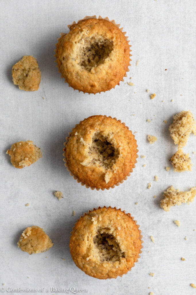 three banana cupcake cored with pieces of cake on the sides on a grey surface