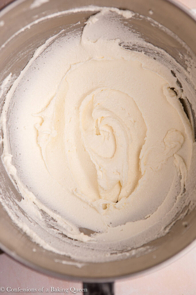 up close of creamed butter, sugar, and oil in a metal mixing bowl on a pink surface
