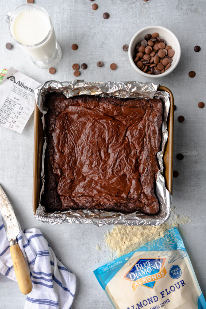 almond flour brownies cooling in pan after baking next to a glass of milk, bowl of chocoalte, knife and linen and bag of almond flour