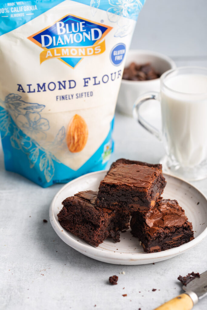 bag of blue diamond almond flour next to a plate of brownies, a glass of milk, and a knife on a light grey surface
