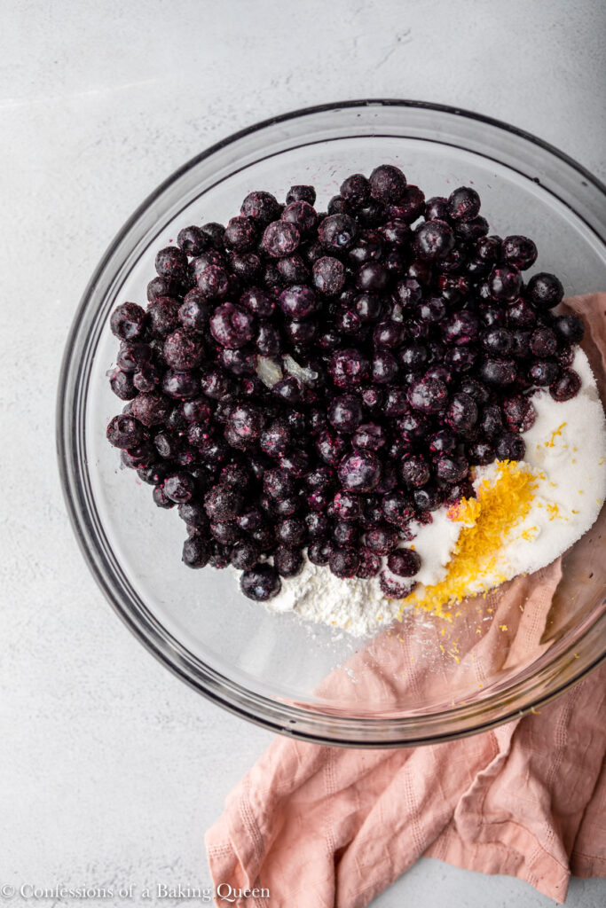 blueberries, sugar, lemon zest, lemon juice, and cornstarch in a large glass bowl on a grey surface with a pink linen
