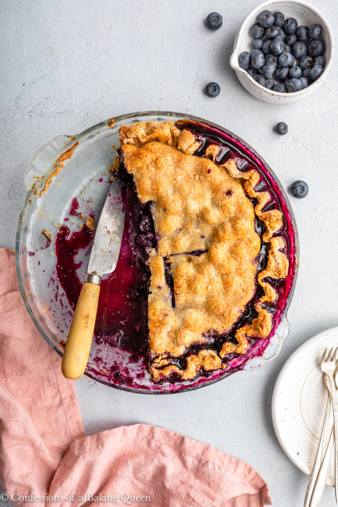 blueberry pie cut up in a glass pie dish with a wooden knife on a grey surface with a pink linen and bowl of blueberries