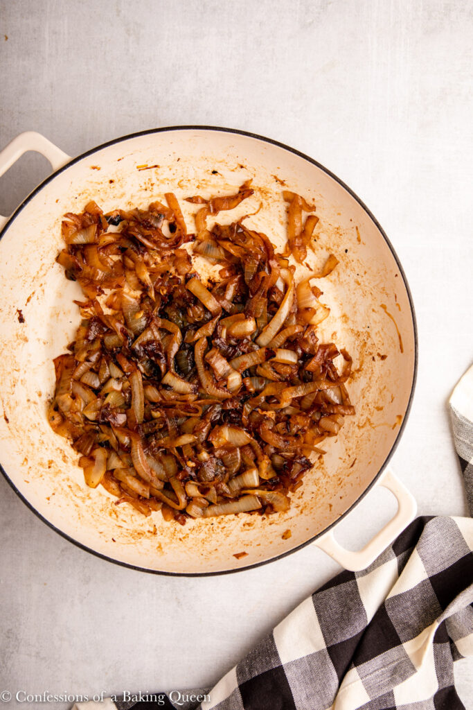 caramelized onions in a white skillet on a grey surface with a white and black checkered towel