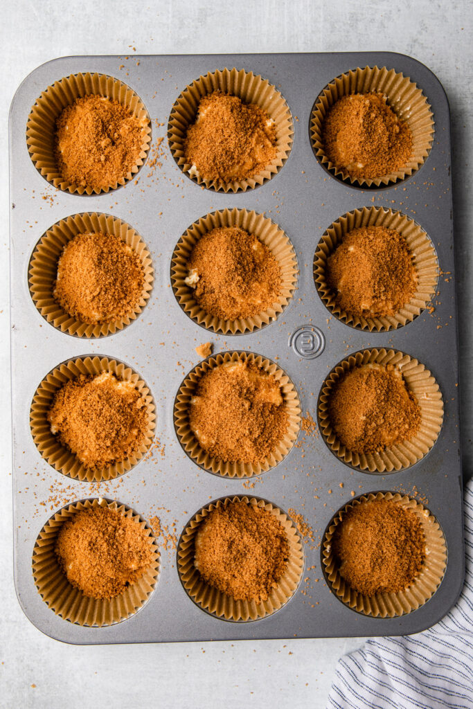 cinnamon sugar added on top of coffee cake batter in a muffin tin on a grey surface with a white and blue linen