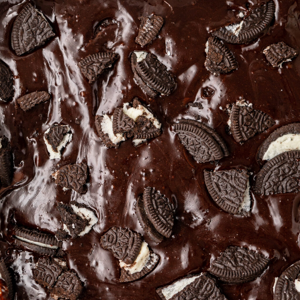 close up of oreo pieces on top of brownie batter