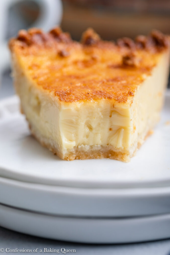 close up of slice of egg custard pie on a stack of three white plates