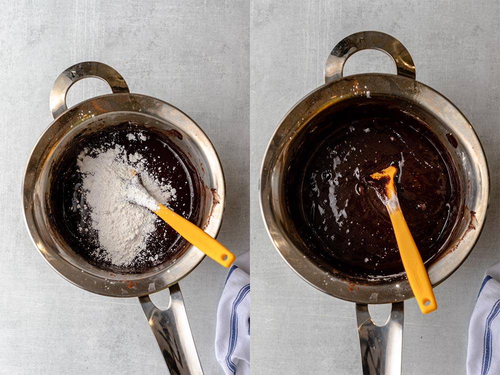 cornstarch, baking powder, and salt added to brownie mixture in a small metal pot on a grey surface