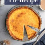 cut open egg custard pie on a wire rack on a grey surface with a cup of tea, plates and forks, slice of pie on a white plate and a navy blue linen with a knife