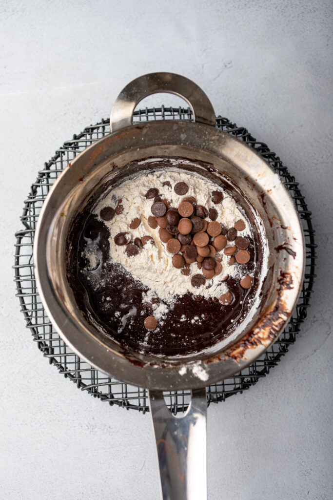 flour and chocolate chips added to brownie batter in a metal pot on a grey surface