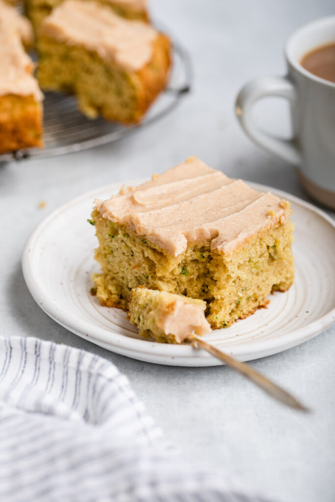 fork taking a bite out of brown butter zucchini snack cake on a small plate next to a cup of coffee on a grey surface