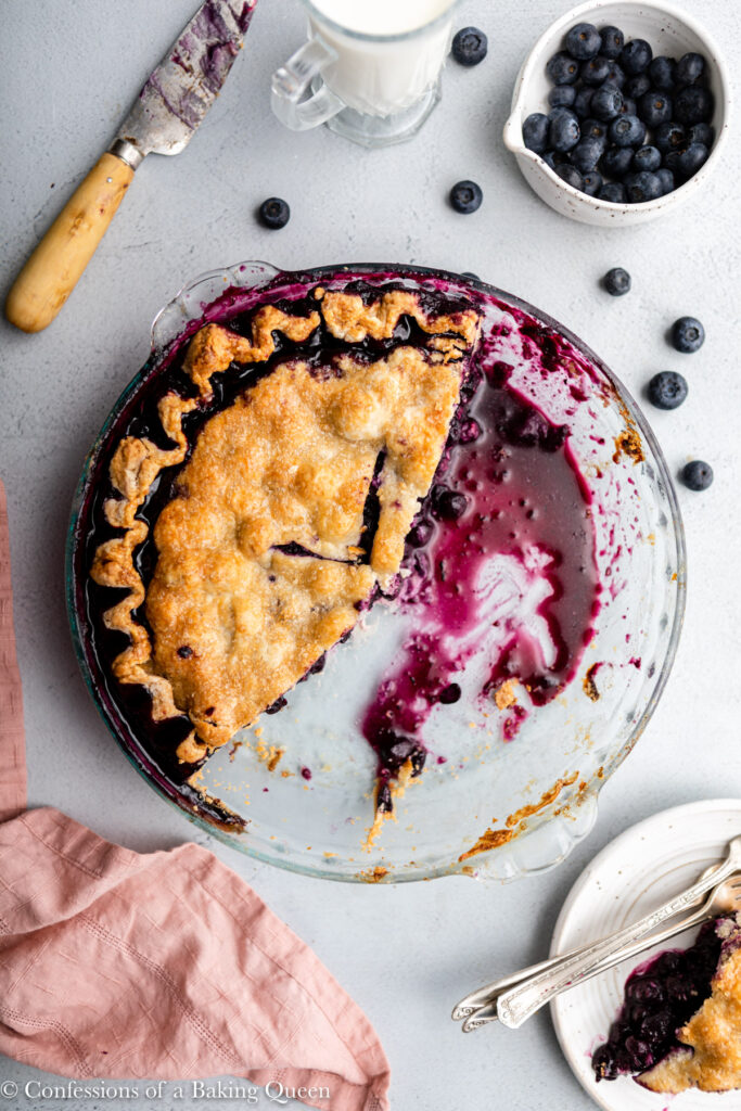 half eaten blueberry pie in a glass dish on a grey surface with a cup of milk, bowl of blueberries, knife, and slice of pie on a plate next to the pie plate