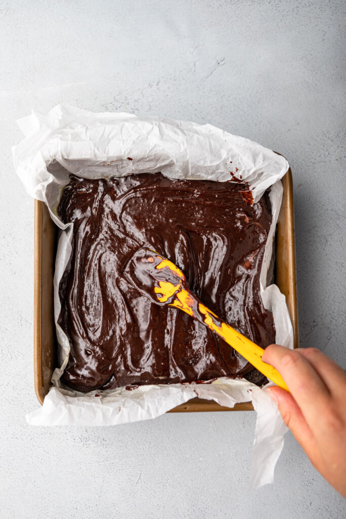 hand holding spatula spreading brownie batter over brownies in a baking pan on a grey surface