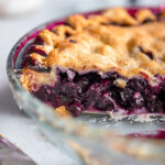 head on view of cut open blueberry pie in a glass dish