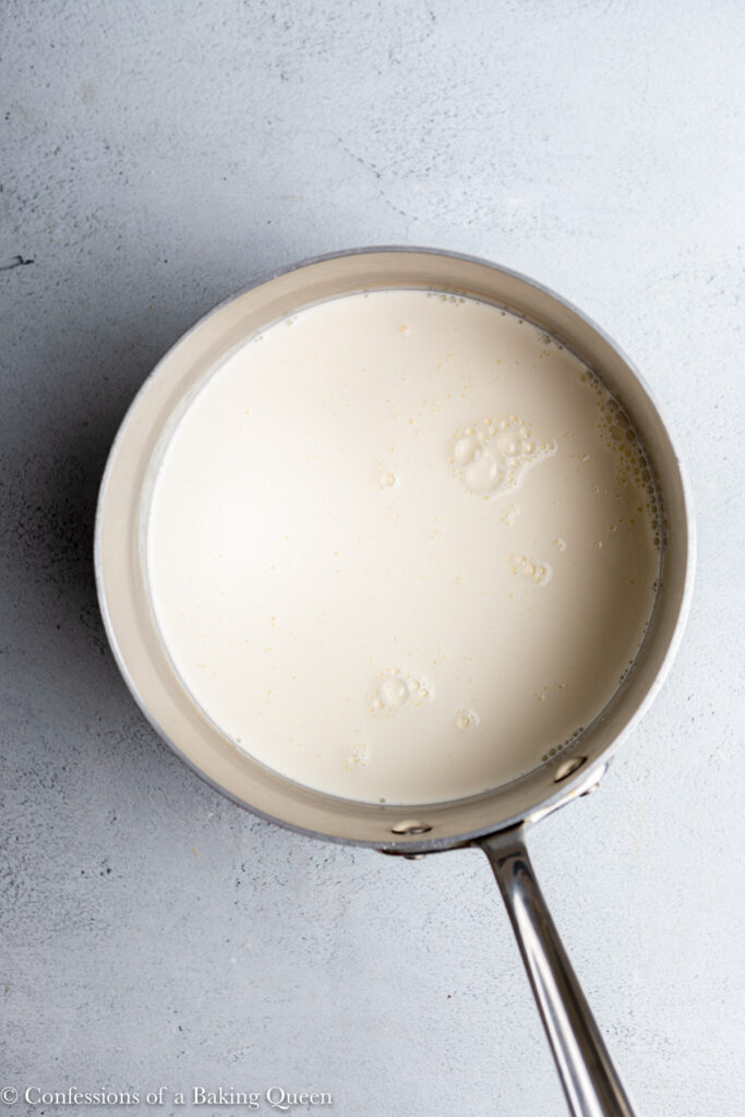 heavy cream and milk warmed in a large saucepan on a grey surface